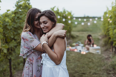 Twin sisters embracing at summer picnic in a vineyard - MAUF01643
