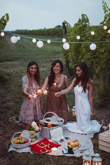 Friends having a picnic in a vinyard, burning sparklers - MAUF01646