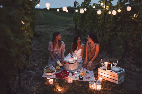 Friends having a picnic in a vineyard on summer night - MAUF01661