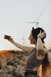 Young woman taking selfie at sunset - OCAF00336