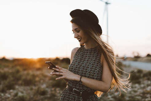 Portrait of young woman looking at cell phone by sunset - OCAF00339