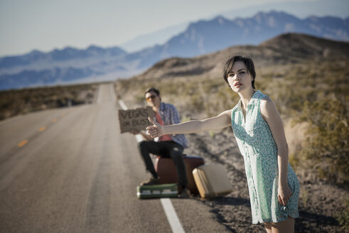 A young couple, man and woman, on a tarmac road in the desert hitchhiking, with a sign saying Vegas or Bust. - MINF03179