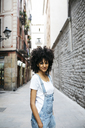 Spain, Barcelona, portrait of smiling woman with curly hair - JRFF01728