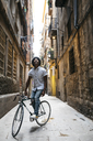 Spain, Barcelona, man standing with racing cycle in an alley looking up - JRFF01734