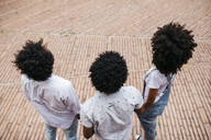 Back view of three friends with curly hair standing on a square - JRFF01740
