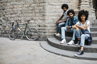 Group of three friends sitting together on stairs in the city - JRFF01743