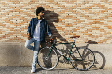 Young man with racing cycle leaning against brick wall - JRFF01746