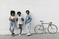 Group of three friends with racing cycle leaning against wall - JRFF01749
