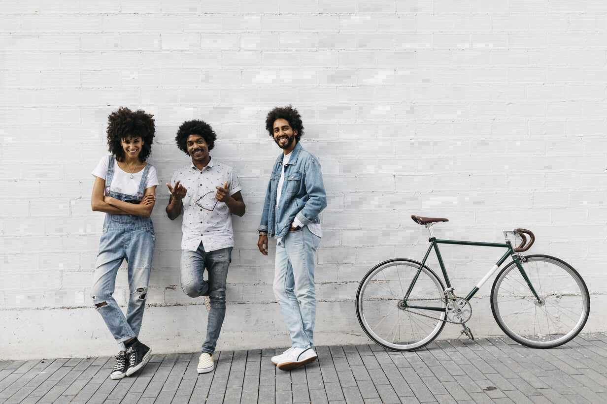 Group of three friends with racing cycle leaning against wall - JRFF01749 - Josep Rovirosa/Westend61