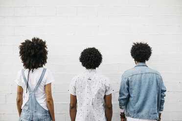 Back view of three friends with curly hair in front of white wall - JRFF01752