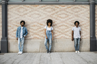 Three friends standing in front of brick wall - JRFF01764