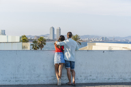 Young couple standing at wall, looking at view - AFVF01163