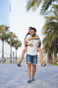 Happy couple in the city, man carrying his girlfriend piggyback - AFVF01193