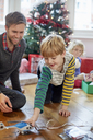 A man and two children finding and unwrapping presents on Christmas day. - MINF03408