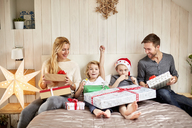 A family, two adults and two children sitting in bed on Christmas morning opening presents together. - MINF03414
