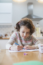A girl sitting at a kitchen table writing a card or letter. - MINF03420
