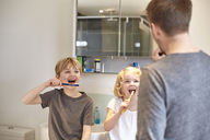 Two children and an adult man cleaning their teeth with toothbrushes in a bathroom. - MINF03492