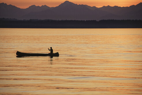 A person seated in a large Indian style canoe paddling across calm water at sunset. - MINF03654
