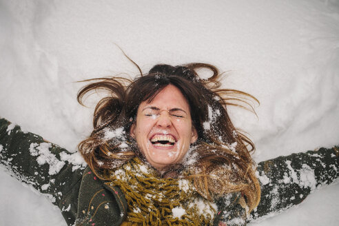A woman lying on a snow bank with her arms stretched out. - MINF03732