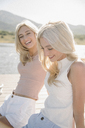 Portrait of two blond sisters sitting on a jetty. - MINF03858