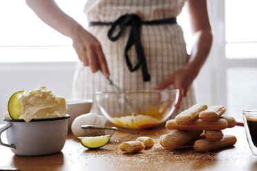 Stack of ladyfingers and cup of  mascarpone on wooden table for preparing Tiramisu - BZF00444