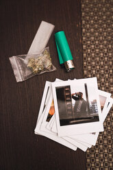Marihuana, cigarette lighter and polaroids on wood - KKAF01345