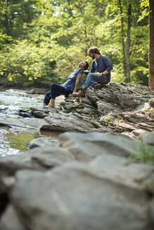 Two men seated in shade on the rocks by the river. - MINF04089