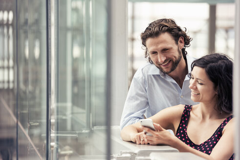 A couple standing together, outside a building with glass exterior, using a smart phone. - MINF04160