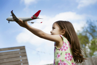 Young girl in garden playing with toy airplane - ISF19618