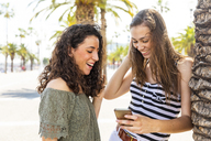 Two happy female friends looking at a smartphone on promenade with palms - WPEF00749