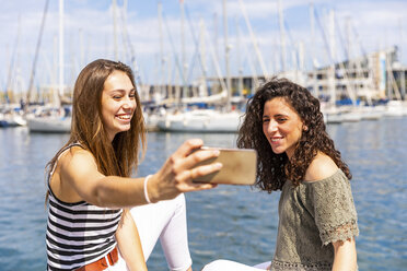 Two happy female friends taking a selfie at a marina - WPEF00755