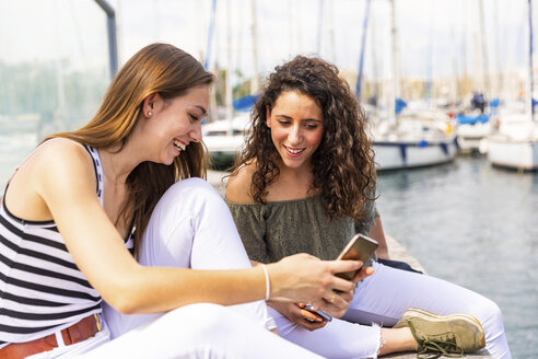 Two happy female friends looking at a smartphone at a marina - WPEF00758