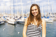 Portrait of smiling young woman at a marina - WPEF00761