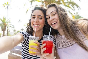Portrait of two happy female friends enjoying a fresh slush - WPEF00764