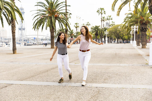 Two happy female friends running on promenade with palms - WPEF00776