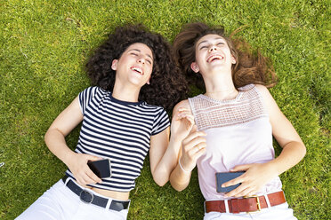 Two happy female friends lying down on grass and having fun - WPEF00779