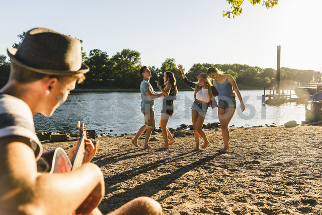 Group of friends having a party at the riverside - UUF14795