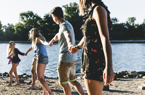 Group of happy friends walking hand in hand at the riverside - UUF14804