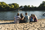 Group of friends sitting at the water looking out - UUF14807