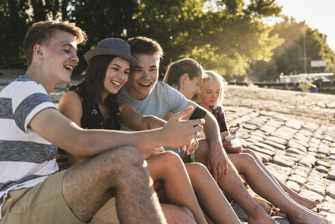 Group of friends sitting on cobblestones with refreshing drinks and cell phones - UUF14813