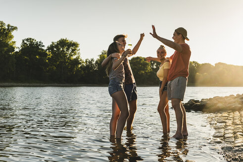 Group of happy friends in a river at sunset - UUF14816
