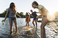 Group of happy friends having fun in a river at sunset - UUF14825