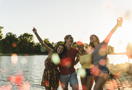 Group of happy friends having fun in a river at sunset - UUF14828