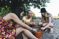 Three young women sitting together having a barbecue - UUF14831