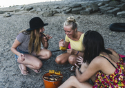 Three young women sitting together having a barbecue - UUF14834