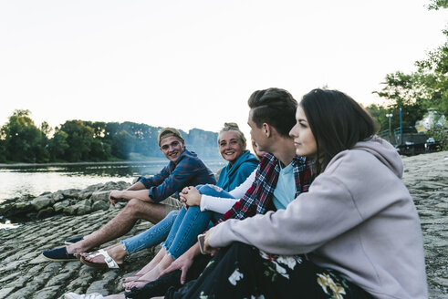 Group of friends sitting at the riverside in the evening - UUF14843