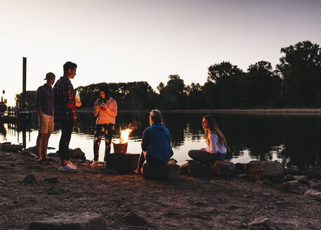 Group of friends at the riverside in the evening - UUF14855