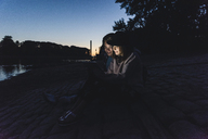 Young couple using tablet at the riverside in the evening - UUF14858