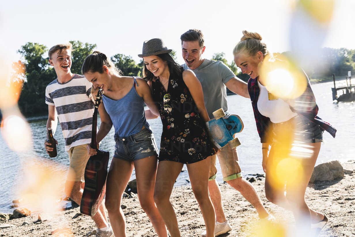 Group of happy friends walking at the riverside - UUF14876 - Uwe Umstätter/Westend61