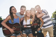 Portrait of group of happy friends with guitar at the riverside - UUF14891